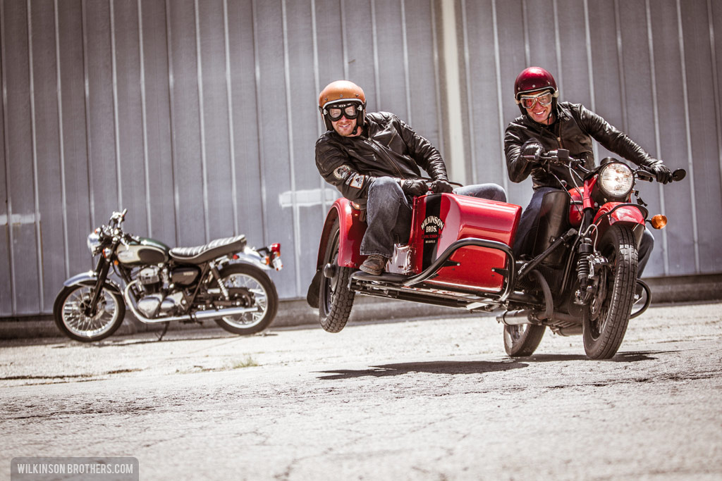 "The Wilkinson Brothers ""flying the chair"" on their Ural Red October sidecar motorcycle."