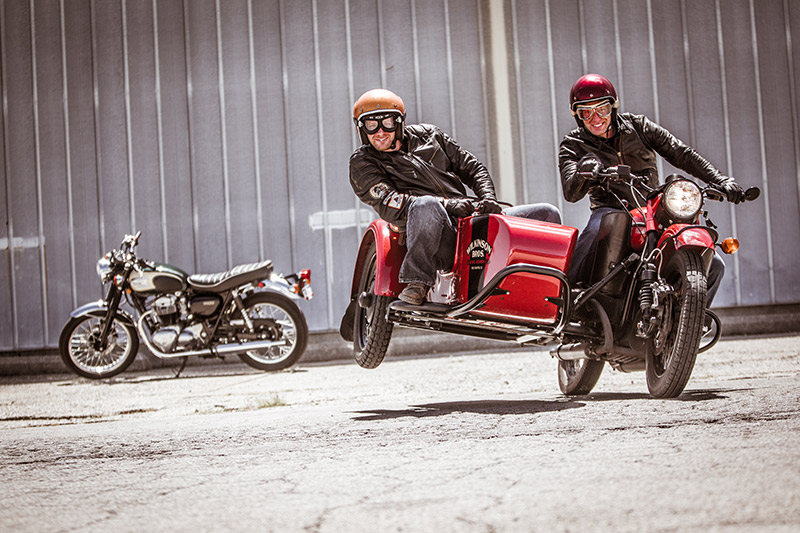 The Wilkinson brothers flying the chair on their Ural motorcycle sidecar.